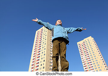 little boy in blue jacket raises his arms to blue sky. In...