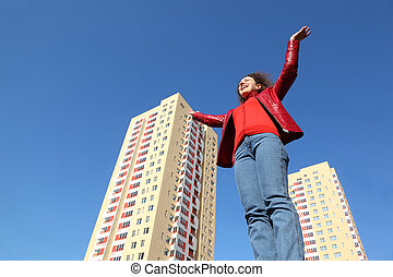 beautiful young woman in red jacket and blue jeans raises his hands to sky. in background two multi-story yellow house