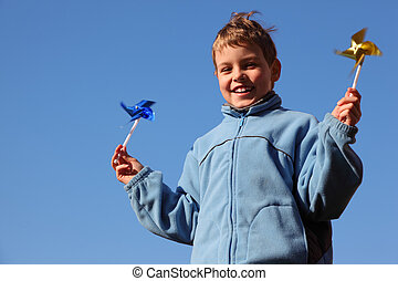 little boy in blue jacket with pinwheels in his hands. blue sky