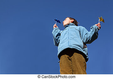 little boy in blue jacket and brown pants blowing on pinwheels in his hands