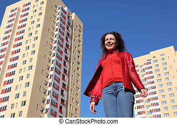 beautiful young woman in red jacket and blue jeans smiling,...