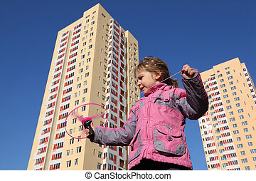 beautiful little girl in pink jacket, plays with propeller....