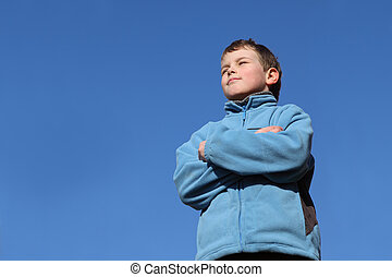 little boy with closed eyes in blue jacket, blue sky, spring