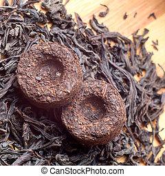 Two bricks of old aroma tea pu-erh on dry tea background