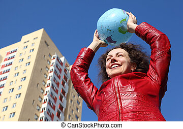 beautiful young woman in red jacket holding balloon in form of globe. multi-storey yellow house