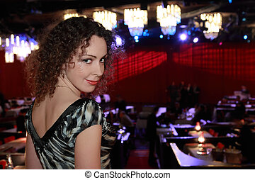 beautiful young woman in evening dress at restaurant, behind