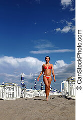 beautiful young woman in bathing suit goes on sand on beach. in background rows of white loungers and blue umbrellas