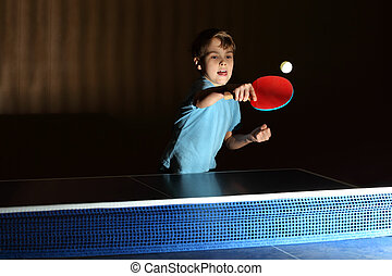 little boy wearing blue shirt playing ping pong;...