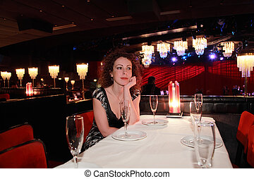 beautiful young woman in evening dress sitting at table at restaurant