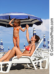 young mother lying on lounger under beach umbrella. little...
