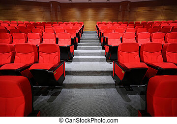Red arm-chairs and gangway are in empty hall