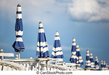 many white loungers and blue beach umbrellas on sand at...