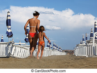 young mother and little daughter in bathing suit going on...