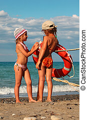 two little sisters in swimsuits standing on beach near metal...