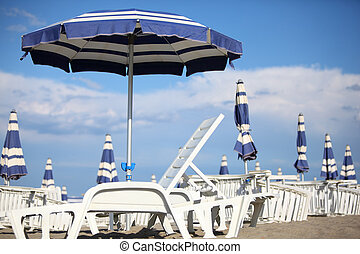 many white loungers and blue beach umbrellas on sand at beach. blue sky and clouds. shallow depth of field