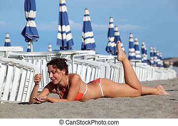 beautiful young woman lying on sand and sunbathe on beach. in background rows of white loungers and blue umbrellas