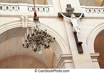 crucifix on marble column in temple and luxurious gilt chandelier, focus on chandelier