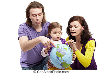 Father and mother show something on the inflatable ball-earth to little daughter, that holds it in her arms.