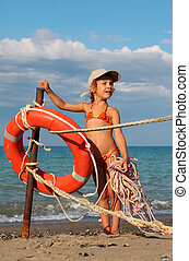 beautiful little girl in bathing suit and cap standing on beach. girl holding rope. red life buoy in frame