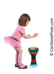 Little girl in pink going to play on the Djembe and put out her tongue from the zeal.