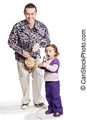 Father plays on the djembe, daughter sings into the microphone.