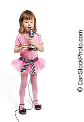 Little girl in pink with microphone sings a song.