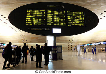 People standing near display board at Charles de Gaulle...