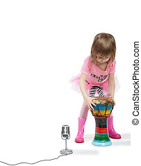Little girl in pink going to play on the Djembe in front of a microphone.