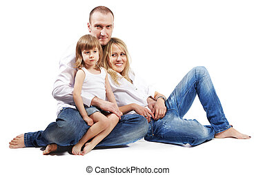 Father, mother and little daughter in white shirts and jeans sit on the floor.