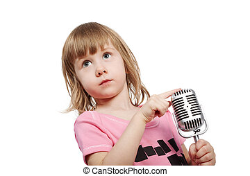Little girl in pink with microphone holds her forefinger on the top of microphone.