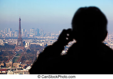 Man photographs panorama of Paris with Eiffel tower, la Defence at winter, France