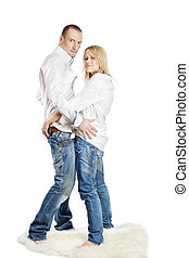 Man and woman in white shirts and blue jeans stand  embraced with turned heads on the white shaggy carpet.