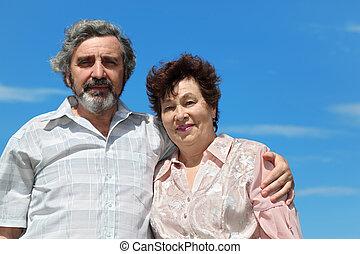 old man embracing woman for shoulder, blue sky
