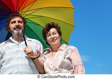 portrait of old woman and man holding multicolored umbrella