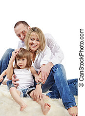 Mother, father and little daughter in the white shirts and blue jeans  sit on the shuggy white carpet.