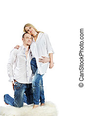 Man and woman in white shirts and blue jeans embrace on the...