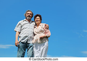old man and woman standing and embracing, blue sky