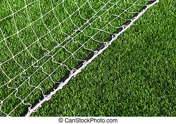 White net for football lying on green artificial grass of football field