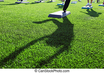 mass fitness at stadium, focus on shadow on green grass; feet and shadow in frame