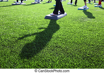 mass fitness at stadium at sunny autumn day, focus on green grass; feet and shadow in frame