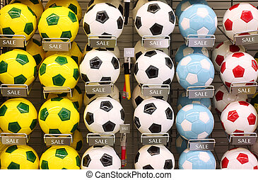 Rows of white, yellow and blue classic soccer balls in store