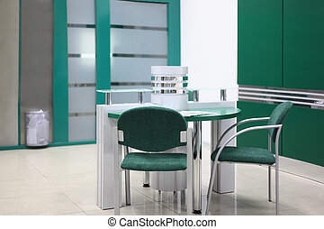 Table and some chairs in clean, simple and empty office with green decoration; focus on chair