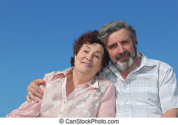 portrait of old man and woman embracing and smiling, blue sky