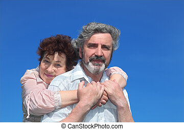 old woman embracing man from back, blue sky