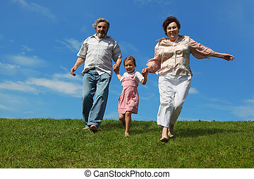barefooted little girl and her grandparents running on...