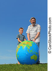 boy and his grandfather standing on lawn near big inflatable globe and smiling
