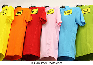 Variety of multicolored casual clothes in shop; T-shirts...