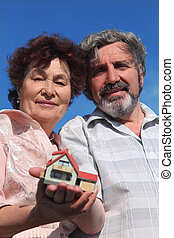 old man and woman holding little model of house, blue sky