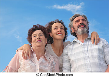 family of adult woman and her parents embracing and smiling, looking up, blue sky