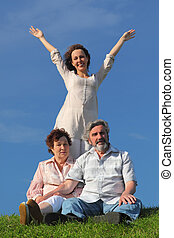 adult daughter with apart hands, her parents sitting on summer lawn